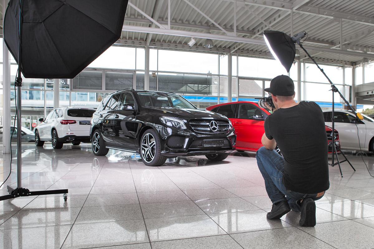 Ein Fotograf erstellt in einem Autohaus Werbeaufnahmen