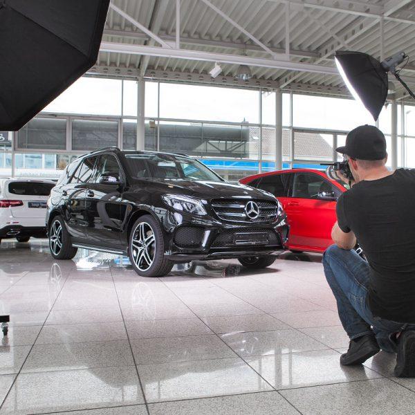 Ein Fotograf fotografiert einen Mercedes für eine Werbeaufnahme